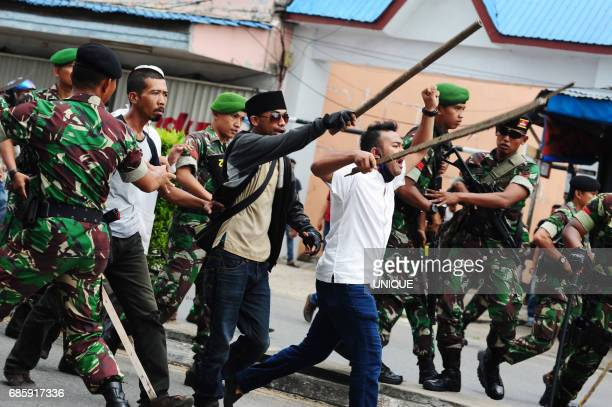 Indonesian hardline Muslim activists are restrained by antiriot police and military personnel as they shout slogans while brandishing wooden sticks...