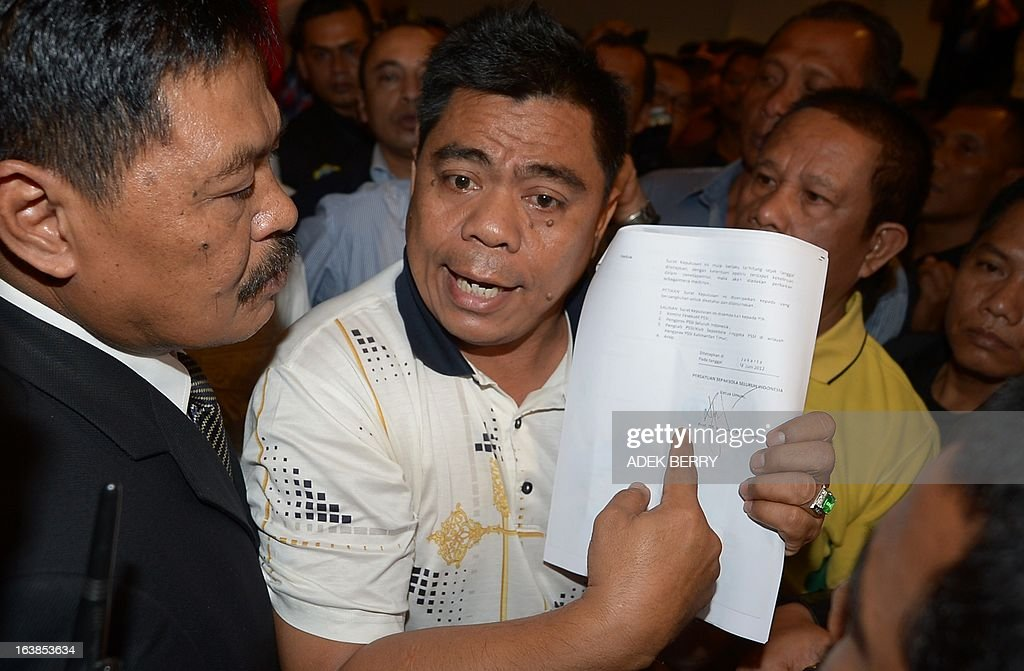 Indonesian Hasan (C), member of Indonesian Football Association (PSSI), of which Djohar Arifin is chairman, holds a document saying his group is legal as members of security prevent them from entering a venue where an extraordinary congress of the PSSI is being held in Jakarta on March 17, 2013. Two rival association of the Indonesian Football Association (PSSI) held an extraordinary congress to avoid looming FIFA sanctions which include a ban on playing international matches. AFP PHOTO / ADEK BERRY