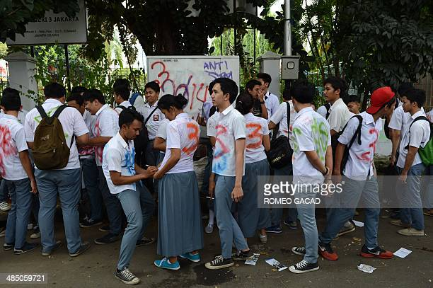 Indonesian high school students celebrate by painting graffiti on their school uniforms after finishing the threeday 2014 national examinations at...