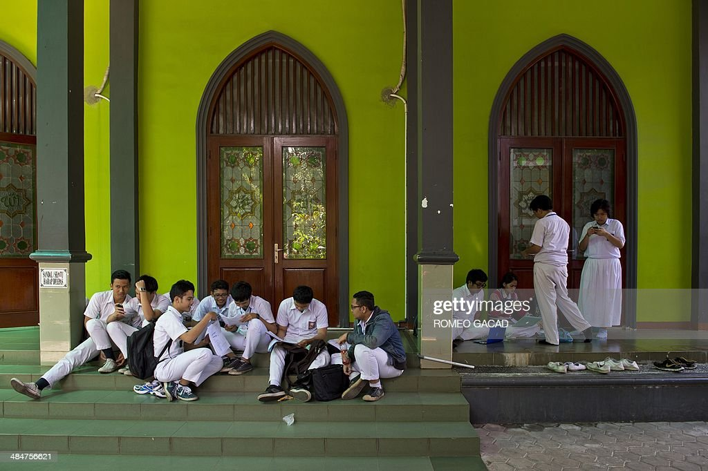 Indonesian high school students do a last minute review in between breaks on the first day of national examinations outside a mosque at a state senior high school compound in Jakarta on April 14, 2014. More than a million students will take part in state senior high school final examinations across Indonesia's 17,000 islands that students are required to pass in order to graduate and continue to higher studies in colleges and universities.