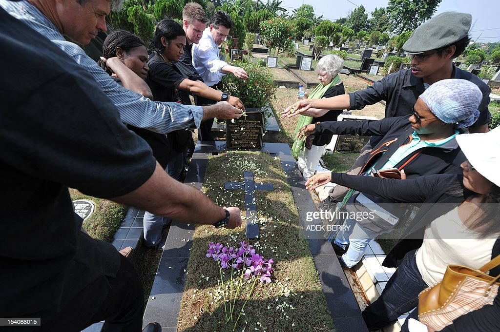 Indonesian journalists along with foreign colleagues sow flowers onto a tomb of five Australian journalist as Australian Shirley Shackleton (C), widow of Australian journalist Greg Shackleton - killed in Balibo in what is now East Timor on October 16, 1975 - looks on at a cemetary in Jakarta on October 14, 2012. Shirley Shackleton has been seeking the return of her husband's remain to Australia for the last 37 years.