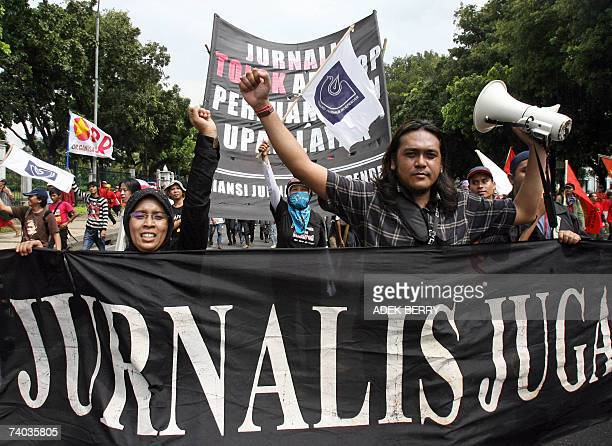 Indonesian journalists raise their hands as they march along with Indonesian labourers during a rally to mark May Day in Jakarta 01 May 2007 Tens of...