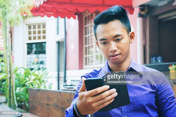 Indonesian man looking at media on his phone outdoors cafe