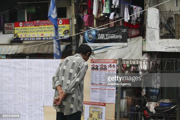 Indonesian man observes the placards of Jakarta Governor candidates during election day to elect Jakarta Governor to a fiveyear term in Jakarta...