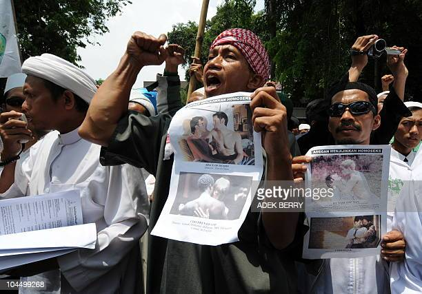 Indonesian members of the hardline Muslim group Front Pembela Islam the Islamic Defender Front hold placards featuring two gay films during a protest...