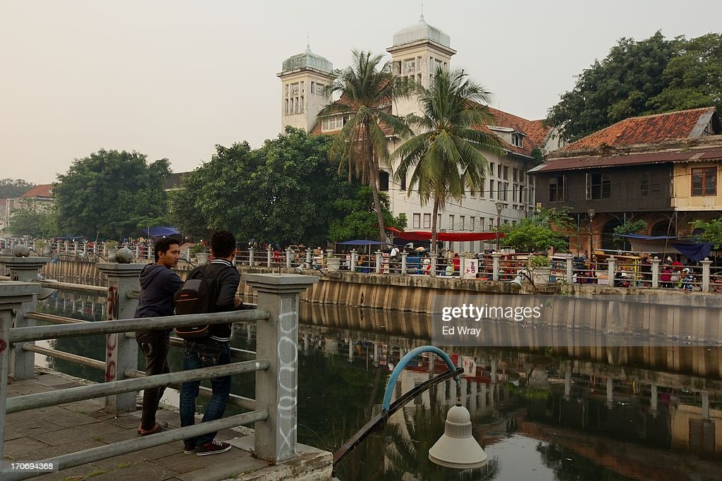 Indonesian men chat overlooking a polluted canal in Kota Tua Sunday June 16, 2013 in Jakarta, Indonesia. Once known as the 'Queen of the East', Kota Tua, which means Old Town in Indonesian, is the original city of Jakarta built by the Dutch in the 16th century and called Batavia at that time. Currently, Kota Tua's beautiful Colonial architecture is in ruins, abandoned as the city edged farther south over the years. Jakarta's Governor, Joko Widodo, hopes to make it a priority to restore the old town and develop it into a high end tourist destination..