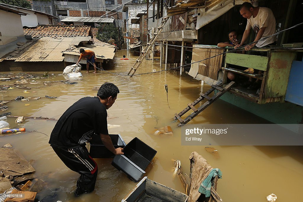 Indonesian men clean and salvage household goods after floodwaters receded enough for them to get to their homes January 19, 2013 in Jakarta, Indonesia. Floodwaters receded today after three days of heavy flooding which left thousands of people's homes underwater. According to Indonesian police the death toll has reached 15.