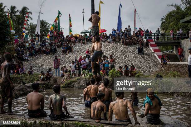 Indonesian men compete for a prize in climbing a greased pole called Panjat Pinang competition during celebrations for the 72nd Indonesia National...