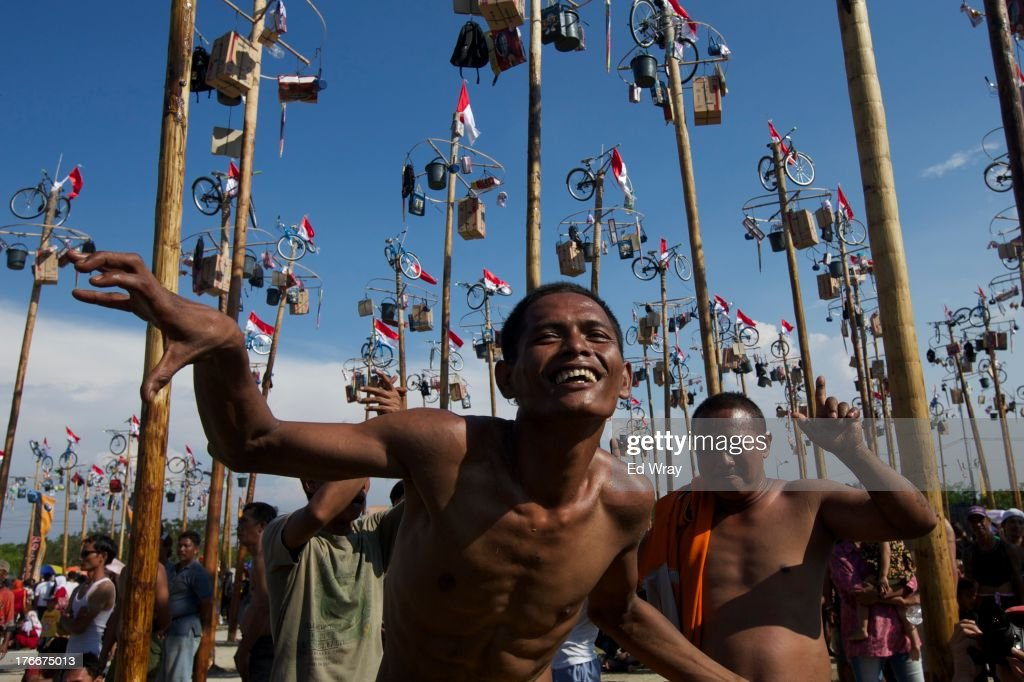 Indonesian men dance before competing in a game, played traditionally on Indonesia's independence day, called panjat pinang in which they try to climb a greased bamboo pole to get prizes such as bicycles and kitchen appliances on August 17, 2013 in Jakarta, Indonesia. Indonesia became an independent nation on 17th August 1945 having previously been under Dutch rule.