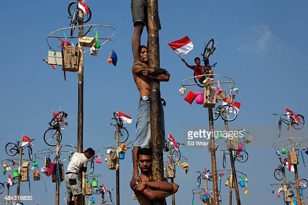 Indonesian men in teams of 4 try to climb to the top of a greased pole called a panjat pinang in order to get to the prizes tied to the top on August...
