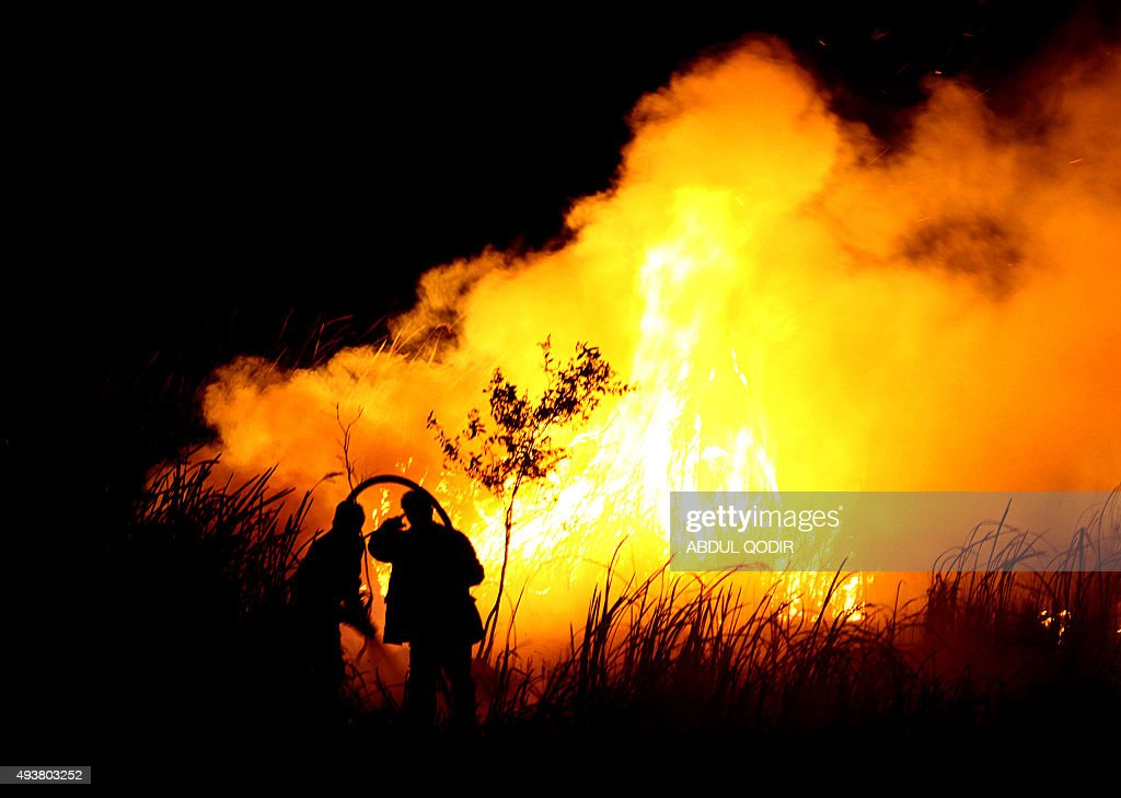 Indonesian men put out a fire in Ogan Ilir southern Sumatra on October 22 2015 Dense haze from Indonesian forest fires has caused some of the worst...