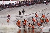 Indonesian men run into the Bengawan Solo river to catch the ducks during duck capture competition within Bengawan Bojonegoro festival in Bojonegoro...