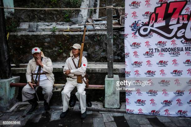 Indonesian men sit wearing japanese soldier costume as they prepare perform a theatrical battle for independence during celebrations for the 72nd...