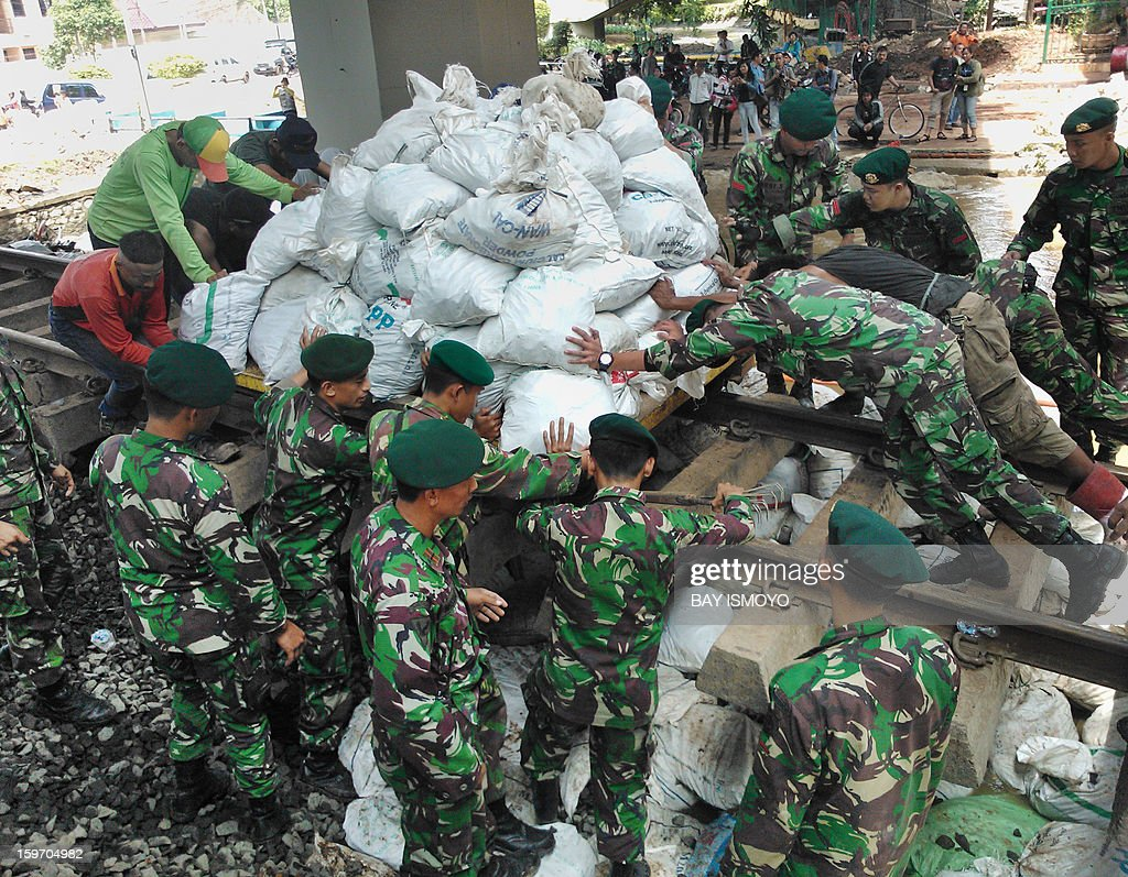 Indonesian military stack sandbags to stop the flow of water from a collapsed river wall in Jakarta on January 19, 2013 after massive flooding hit the capital on January 17. The death toll from floods in Indonesia's capital Jakarta has risen to 15 after rescuers found another four bodies, a police spokesman said, as floodwaters receded. AFP PHOTO / Bay ISMOYO