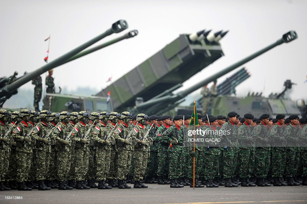 Indonesian military troops stand in formation in front of 155mm canons and multiple launcher rocket system weaponry as President Susilo Bambang Yudhoyono leads celebrations marking the 67th anniversary of the Indonesian armed forces at Halim Perdana Kusumah airport in Jakarta on October 5, 2012.