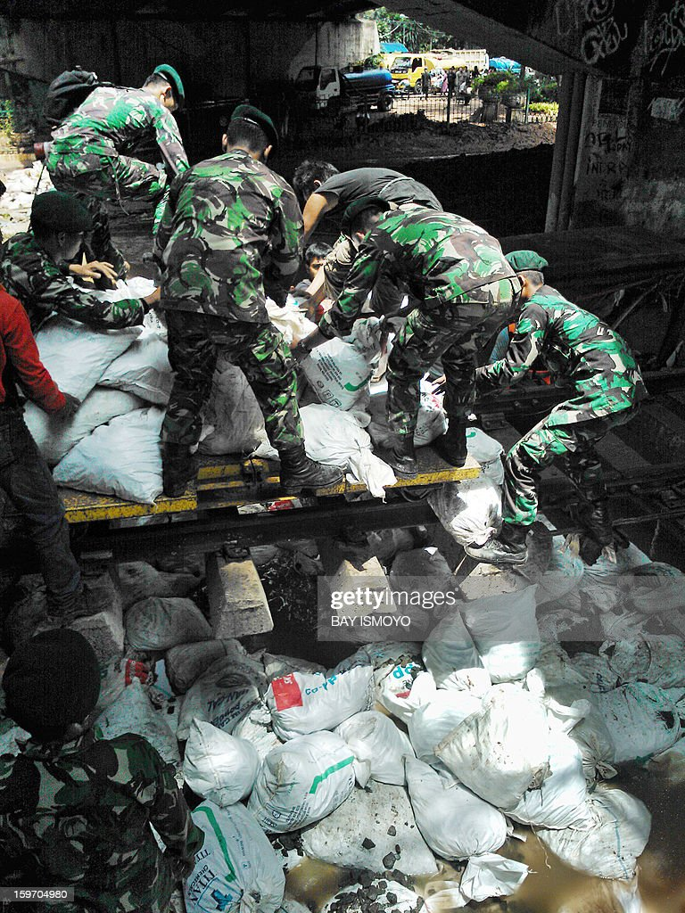 Indonesian military unload sandbags to stop the flow of water from a collapsed river wall in Jakarta on January 19, 2013 after massive flooding hit the capital on January 17. The death toll from floods in Indonesia's capital Jakarta has risen to 15 after rescuers found another four bodies, a police spokesman said, as floodwaters receded. AFP PHOTO / Bay ISMOYO