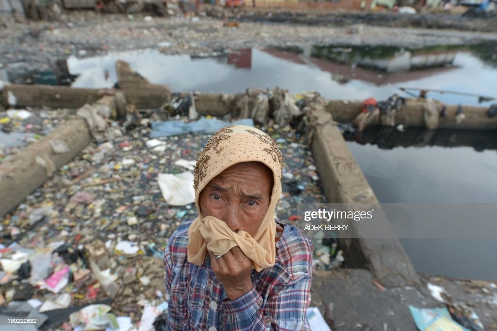 Indonesian Misriati stands next to the Pluit dam, that is full of garbage in Jakarta on January 28, 2013. AFP PHOTO / ADEK BERRY