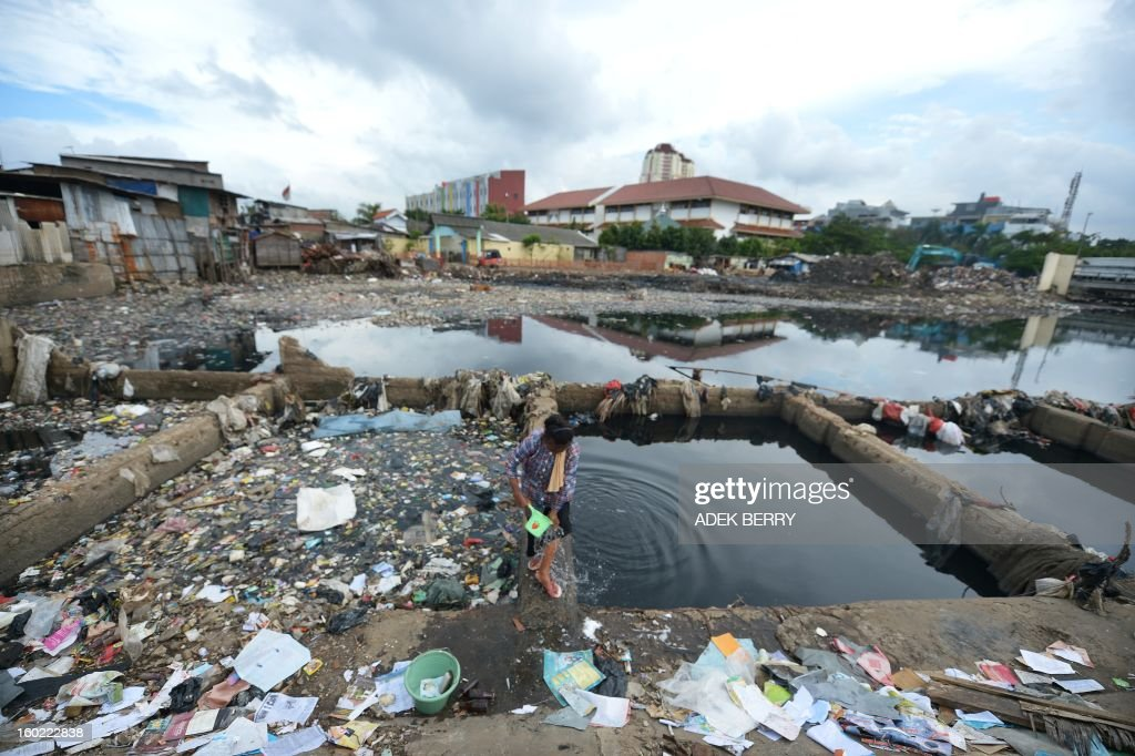 Indonesian Misriati uses polluted water from the Pluit dam that is brimming with garbage in Jakarta on January 28, 2013.