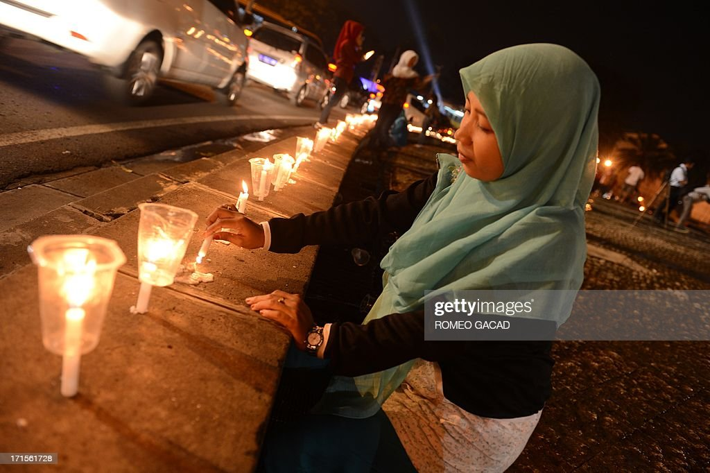 Indonesian mother Cherry (L) and son Yobel (2L) light candles during an anti-drug campaign action at the Jakarta's Bunderan HI monument to mark the UN's international day against drug abuse and illicit trafficking on June 26, 2013. Indonesian President Susilo Bambang Yudhoyono in his June 24, 2013 address to mark International Day Against Drug Abuse campaigned against the punishment of drug user but called for rehabilitation. According to the Ministry of Justice more than 40 percent of around 150,000 people in Indonesian prisons are detained for drug offenses.