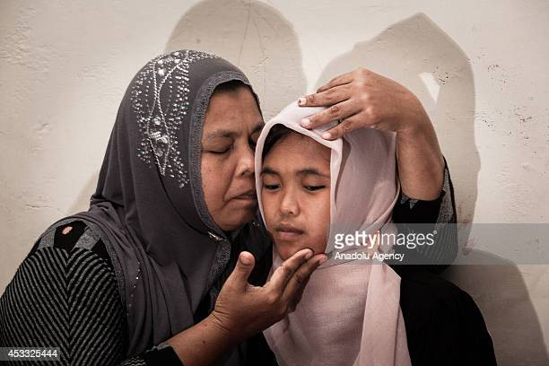 Indonesian mother Jamaliah hugs her daughter Raudhatul Jannah after they were reunited in Meulaboh Aceh Indonesia on August 7 2014 Raudhatul Jannah...