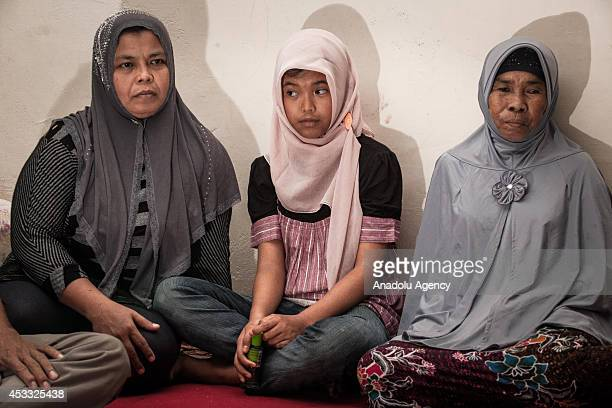 Indonesian mother Jamaliah sits next to her daughter Raudhatul Jannah after they were reunited in Meulaboh Aceh Indonesia on August 7 2014 Raudhatul...