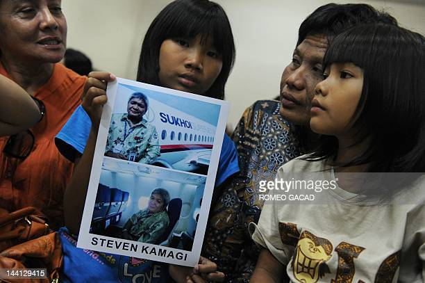 Indonesian mother Muawana and her two daughters Tashia and Olivia display a photograph of her missing husband Steven Kamagi taken aboard the ill...