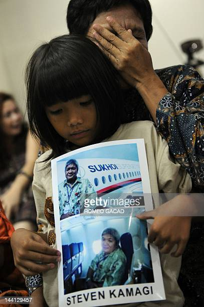 Indonesian mother Muawana sits with her daughter Olivia holding a photograph of her missing husband Steven Kamagi taken aboard the ill fated Russian...