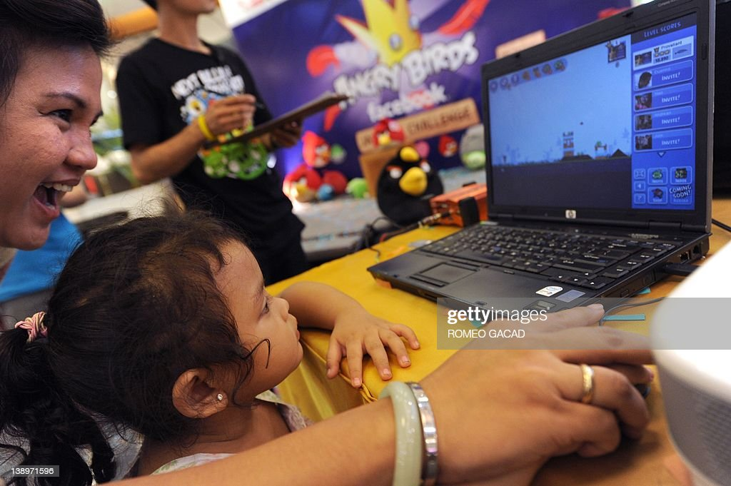 Indonesian mother Novi Yacob guides her three-year-old daughter Karina Maharani as they play the 'Angry Birds' during the official Facebook launch at a mall in the Indonesian capital city of Jakarta on February 14, 2012. 'Angry Birds', the most-downloaded mobile app of 2011, was catapulted to the world of Facebook on February 14 in a bid by its Finnish maker Rovio to get one billion people playing the addictive game.