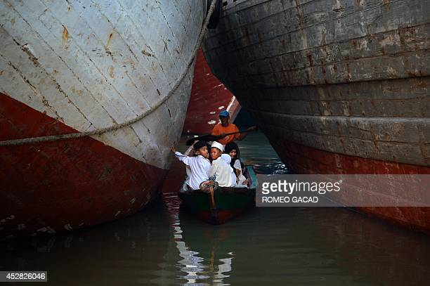 Indonesian Muslim devotees arrive on a boat to attend the morning prayer to celebrate the Eid alFitr festival at the historic Sunda Kelapa port...