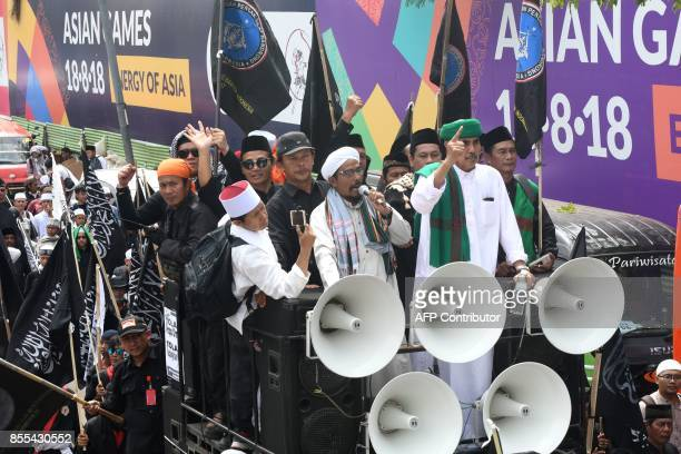 Indonesian Muslim leaders urge their followers to march on as they carry flags and banners toward Parliament building to mark the 52nd anniversary of...