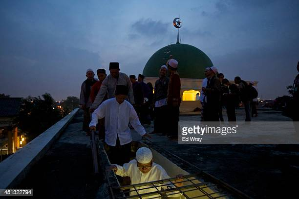 Indonesian Muslim men pray come down from the roof of a mosque after trying to sight the new moon the sign of the start of the Islamic holy month...