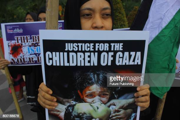 Indonesian Muslim protesters shout slogans and hold banner in support of Palestine during the International AlQuds day in front of the US Embassy on...