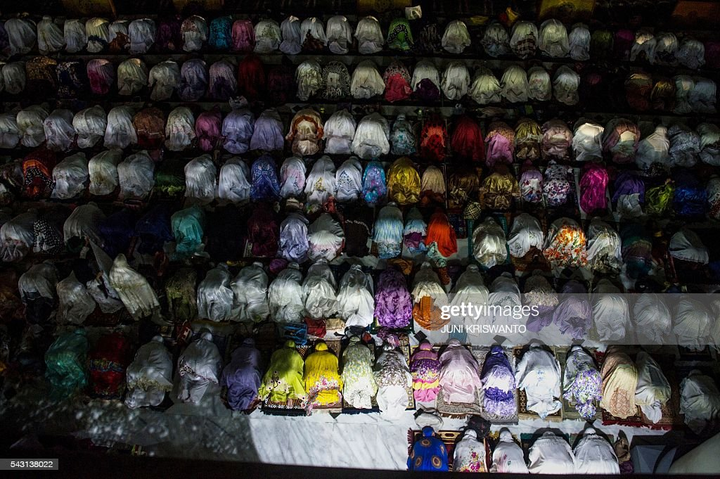 Indonesian Muslim women offer prayers on the 21th night of holy month of Ramadan at a mosque in the city of Surabaya early on June 26, 2016. Muslims throughout the world are marking the month of Ramadan, the holiest month in the Islamic calendar, during which devotees fast from dawn until dusk. / AFP / JUNI