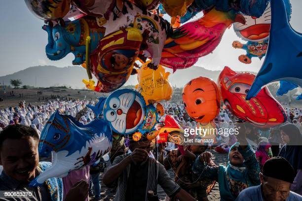 Indonesian Muslims buy balloons as attend Eid AlFitr prayer on 'sea of sands' at Parangkusumo beach on June 25 2017 in Yogyakarta Indonesia Eid...