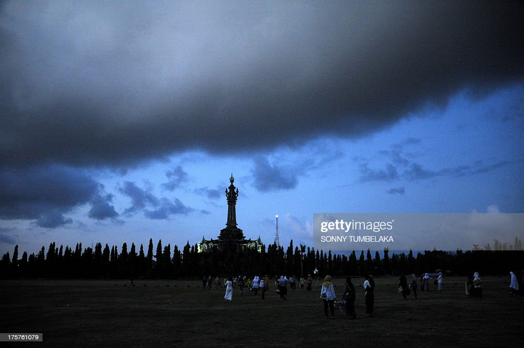 Indonesian Muslims gather early morning to take part in special morning prayers near the Bajrah Sandhi monument in Denpasar on Indonesia's island of Bali on August 8, 2013. Muslims around the world will celebrate Eid al-Fitr this week, marking the end of holiest month of Ramadan during which followers are required to abstain from food, drink and sex from dawn to dusk.