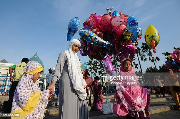 Indonesian Muslims kids buy toys after perform Eid AlAdha prayers at AlAkbar Mosque on October 5 2014 in Surabaya Indonesia Muslims worldwide...