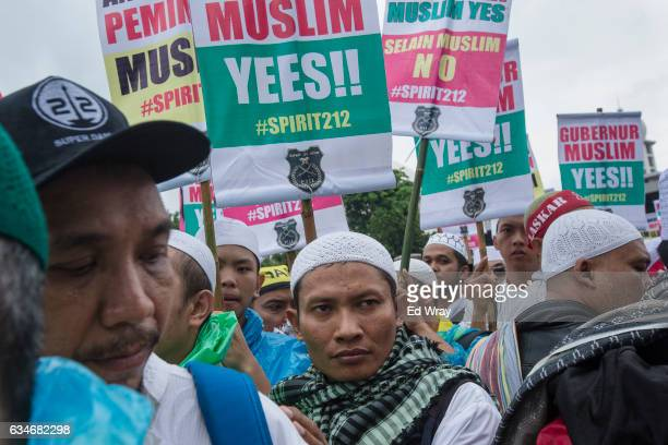 Indonesian Muslims men walk past signs during a mass prayer rally of tens of thousands of Muslimss calling for people to elect a Muslims Governor of...