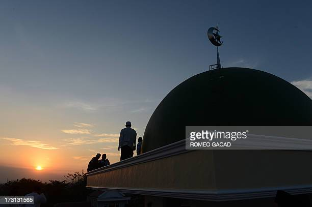 Indonesian Muslims prepare to sight the new moon from the rooftop of the AlHidayah Basmol mosque in Jakarta on July 8 2013 in preparation for the...