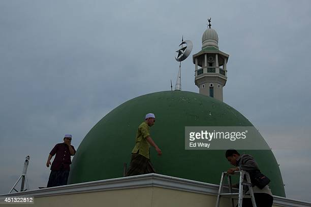 Indonesian Muslims prepare to sight the new moon from the top of a mosque the sign of the start of the Islamic holy month Ramadan on June 27 2014 in...