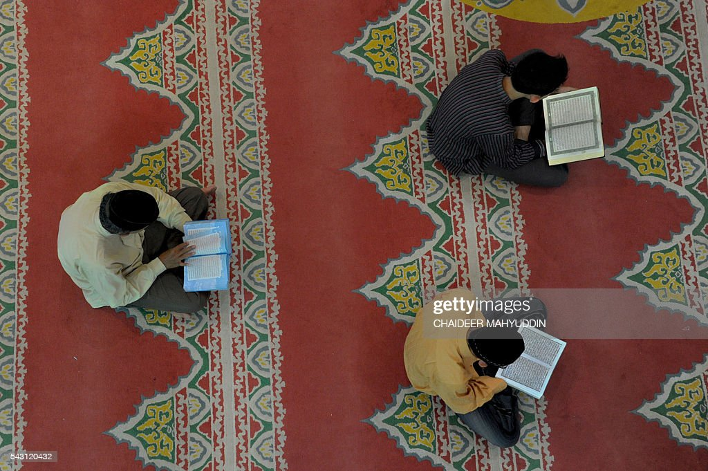 Indonesian Muslims read copies of the Koran at the Al Makmur mosque in Banda Aceh on June 26, 2016. Muslims throughout the world are marking the month of Ramadan, the holiest month in the Islamic calendar, during which devotees fast from dawn until dusk. / AFP / CHAIDEER