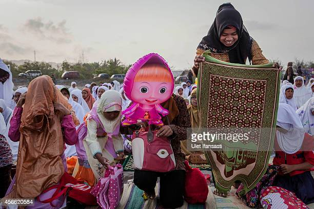 Indonesian muslims smile as they attend prayer on the 'sea of sands' as they prepare for Eid AlAdha prayer at Parangkusumo beach on October 4 2014 in...