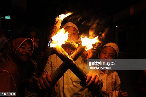 Indonesian Muslims students carry torches as they parade on the streets ahead of Eid AlAdha on September 24 2015 in Surabaya Indonesia Muslims...