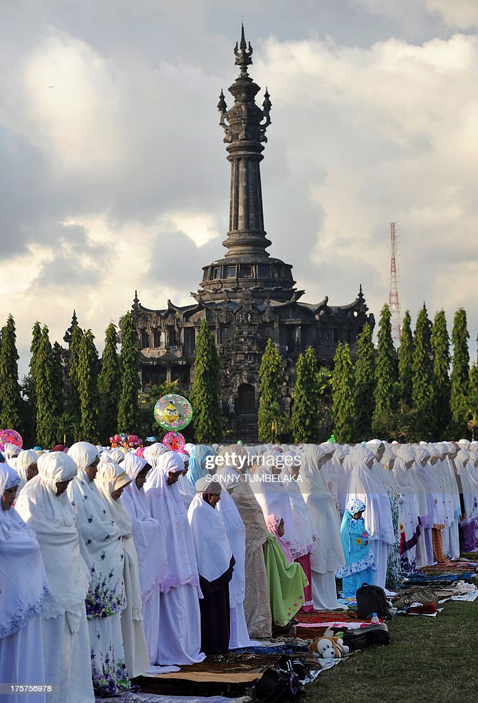 Indonesian Muslims take part in special morning prayers near the Bajrah Sandhi monument in Denpasar on Indonesia's island of Bali on August 8, 2013. Muslims around the world will celebrate Eid al-Fitr this week, marking the end of holiest month of Ramadan during which followers are required to abstain from food, drink and sex from dawn to dusk. AFP PHOTO / SONNY TUMBELAKA