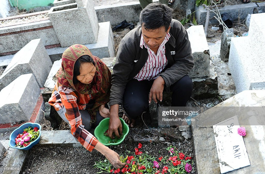 Indonesian Muslims visit the graves of family members, bringing offerings flowers and praying before Ramadan on July 9, 2013 in Surabaya, Indonesia. Muslims fasting in the month of Ramadan abstain from food, drink and sex from dawn until sunset, when they break the fast with the meal known as Iftar.