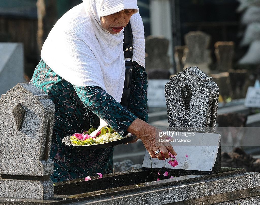 Indonesian Muslims visit the graves of family members, bringing offerings of flowers and praying before Ramadan on July 9, 2013 in Surabaya, Indonesia. Muslims fasting in the month of Ramadan abstain from food, drink and sex from dawn until sunset, when they break the fast with the meal known as Iftar.