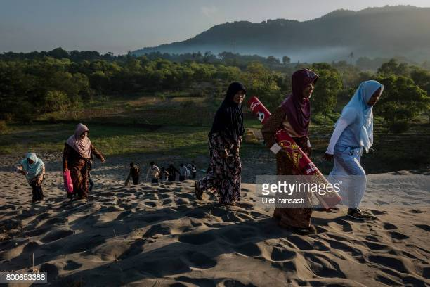Indonesian Muslims walk on 'sea of sands' as they prepare for Eid AlFitr prayer at Parangkusumo beach on June 25 2017 in Yogyakarta Indonesia Eid...