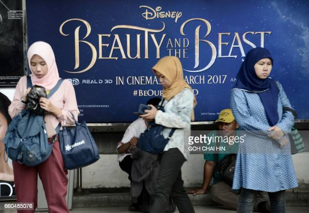 Indonesian Muslims walk past a poster of Disney's blockbuster 'Beauty and the Beast' now showing in cinemas in Jakarta on March 30 2017 Disney...