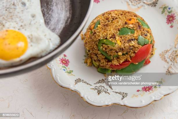 Indonesian nasi goreng with bumbu on a decorative plate.