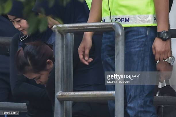 Indonesian national Siti Aisyah is escorted by Malaysian police after a court appearance with Vietnamese national Doan Thi Huong at the magistrates'...