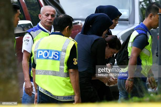 Indonesian national Siti Aisyah is escorted by Malaysian police for a court appearance with Vietnamese national Doan Thi Huong at the Sepang...